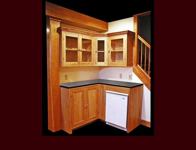 Custom Oak Kitchenette. Flat Panel door style. Glass door upper cabinets. Crown Moulding.