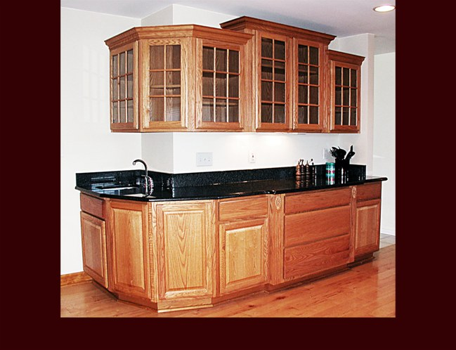 Custom Oak Kitchen. Raised Panel door style. Multi-level glass door upper cabinets. Bar sink. Extended depth pots & pans drawer cabinet. Crown Moulding. Light Rail.
