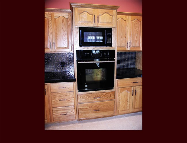 Custom Oak Kitchen Remodel. Raised Panel Cathedral door style. Full height wall oven cabinet with full extension pots & pans drawers and upper storage. Crown Moulding.
